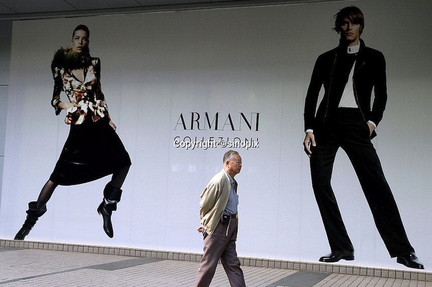Man passing advertising for luxury fashion brand Armani at a shopping mall on Nanjing Xi Lu in Shanghai, China..