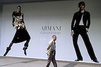 Man passing advertising for luxury fashion brand Armani at a shopping mall on Nanjing Xi Lu in Shanghai, China..