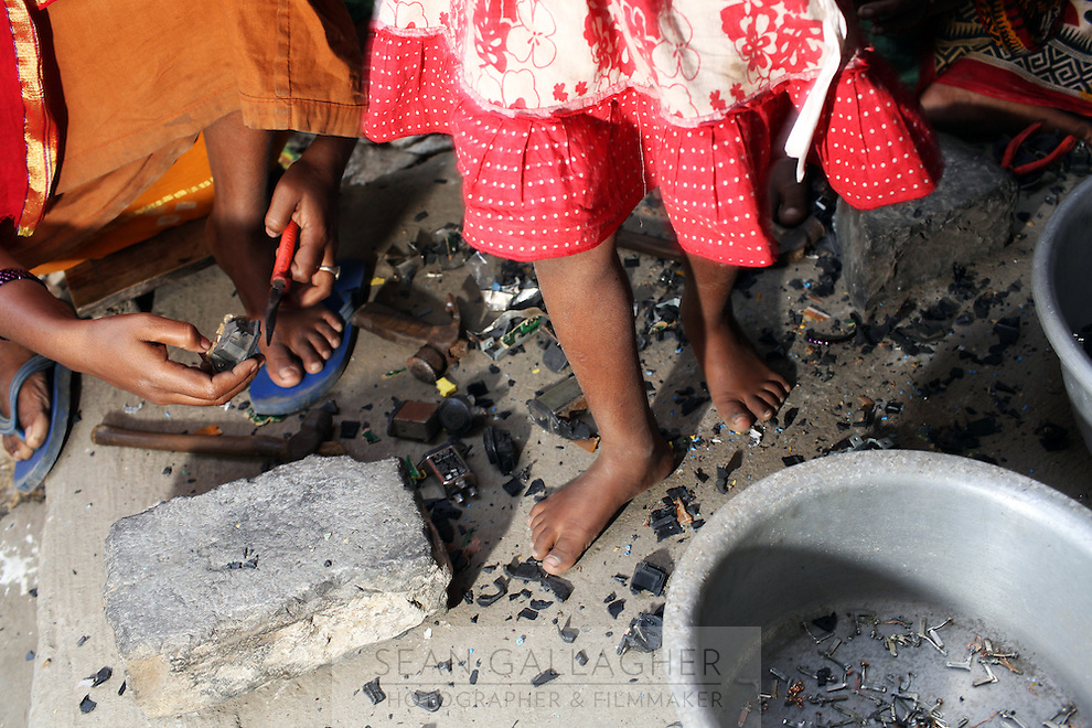 A young girl walks barefoot over e-waste, which her family is breaking down to recycle in the village of Sangrampur, near Kolkata. India. November, 2013