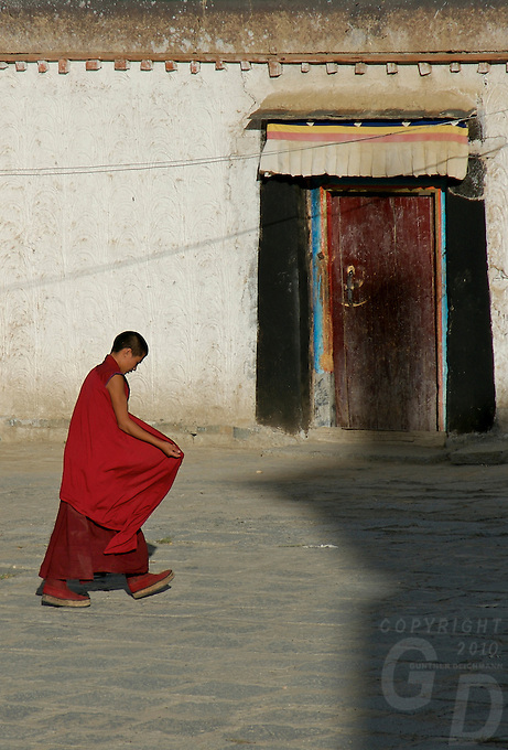 Buddhist Monks walking in the afternoon through the courtyard of the Monestary