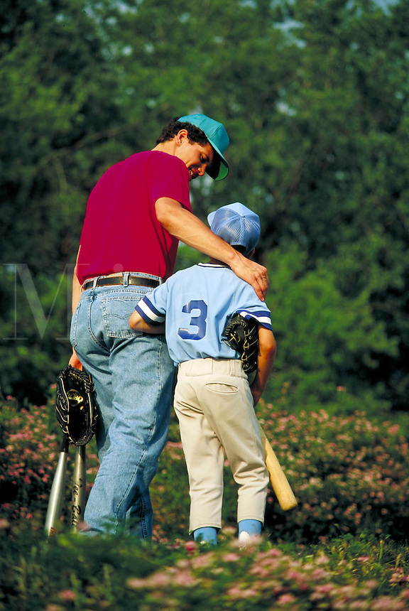 Father puts his arm around his son, aged 10-12 dressed in baseball uniform and carrying glove and bat as they leave practice. father and son or coach and little leaguer.