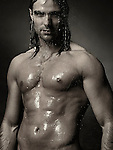 Dramatic portrait of a young man with wet bare torso standing under a shower with water running down his body. Black and white sepia toned; Image © MaximImages, License at https://www.maximimages.com