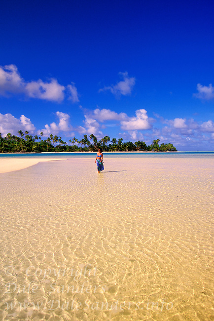 Woman  walking down a beautiful beach on an uninhabited island in Aitutaki Lagoon, Cook Islands, in the South Pacific.  Model Released