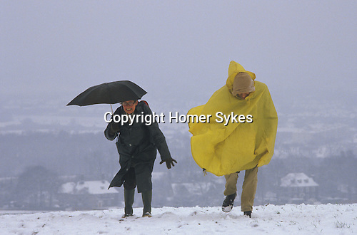 South Downs, Sussex. 1980s<br /> Two old age pensioners on a Ramblers Association walk battle against snow and wind, nearly being blown away.