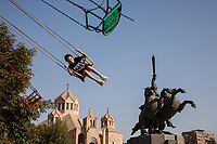 Armenia. Yerevan. A young girl is seated on a high speed carousel swing. The Saint Gregory the Illuminator Cathedral and the equestrian statue of Andranik. The Saint Gregory the Illuminator Cathedral, also known as the Yerevan Cathedral is currently the largest cathedral of the Armenian Apostolic Church in the world. The Armenian Apostolic Church is the national church of the Armenian people. Part of Oriental Orthodoxy, it is one of the most ancient Christian communities. Andranik Ozanian, commonly known as Andranik (25 February 1865 – 31 August 1927) was an Armenian military commander and statesman, the best known fedayi and a key figure of the Armenian national liberation movement. From the late 19th century to the early 20th century, he was one of the main Armenian leaders of military efforts for the independence of Armenia. Yerevan, sometimes spelled Erevan, is the capital and largest city of Armenia. 10.10.2019 © 2019 Didier Ruef