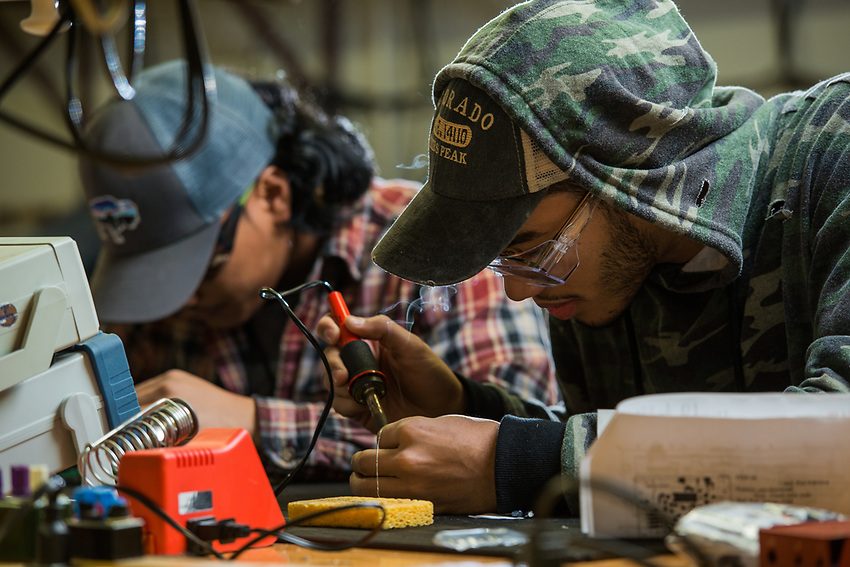 Aviation Maintenance Technology students Roland Rodriguez, right, and Desmond Corpuz, left, practice soldering during AMT 272 Aircraft Electrical Hardware and Systems at UAA's Aviation Technology Center.