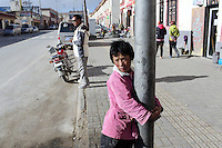A young girl holds onto a lamppost in a Tibetan community on the Tibetan Plateau, in western China.