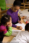 Education preschool 4 year olds art activity female teacher working with girl teacher is talking and working on her own drawing vertical
