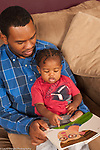 17 month old toddler boy sitting in father's lap, read to, pointing at illustration in picture book