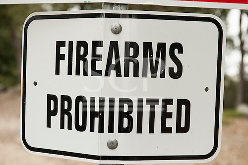"""California, USA. Bent damaged """"Firearms Prohibited"""" road sign."""