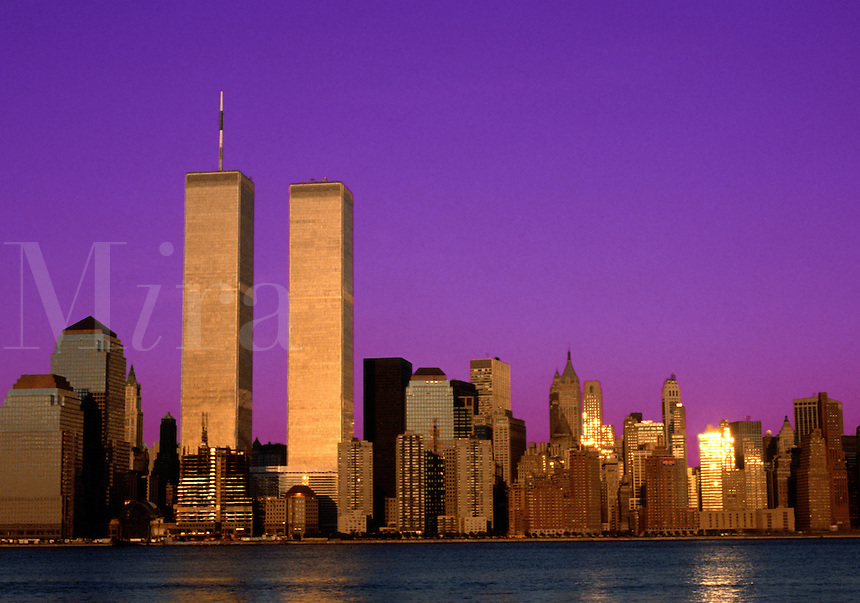 The New York City skyline at dusk featuring the twin towers of the World Trade Center.