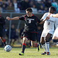 Northeastern University forward Donovan Fayd'Herbe de Maudave (9) on the attack as University of Connecticut midfielder George Fochive (9) defends..NCAA Tournament. University of Connecticut (white) defeated Northeastern University (black), 1-0, at Morrone Stadium at University of Connecticut on November 18, 2012.