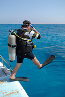 scuba diver with his BCD inflated doing a giant stride to enter into the water, Egypt, Red Sea