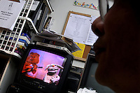"""Richard J. Concepcion, aka Rapid T. Rabbit , watches a video in his apartment in Queens, New York, from an early episode of his cable access television show """"Rapid T. Rabbit and Friends""""."""