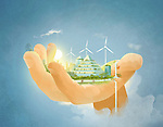 Illustrative image of building and wind turbines in human hand representing environment conservation