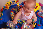 8 month old baby girl old in walker/stander reaching to spin toy walker is stationary