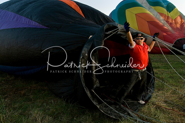 A man steadies a balloon as it's being filled with hot air. Thousands of hot air balloon enthusiasts turn out each year for the annual Carolina BalloonFest, held each fall in Statesville, NC. Photos were taken at the October 2008 event.