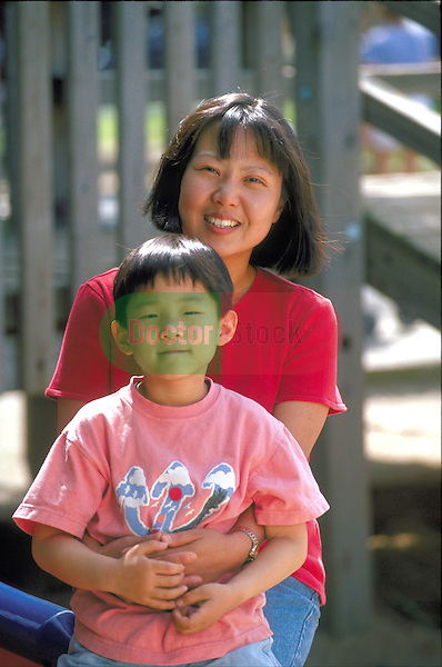 portrait of smiling mother with boy in park