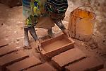 nella periferia di Ouagadougou in Burkina Faso uno dei tanti spazi aridi trasformato in cava-fabbrica i mattoni crudi di fango. Qui lavorano prevalentemente donne e bambini delle comunità che abitano intorno alla cava.