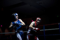 Two male boxers fight in the ring at the London Irish Centre where the 'Carpe Diem' white collar boxing event is taking place. <br /> <br /> 'White-collar boxing' is a growing phenomenon amongst well paid office workers and professionals and has seen particular growth in financial centres like London, Hong Kong and Shanghai. It started at a blue-collar gym in Brooklyn in 1988 with a bout between an attorney and an academic and has since spread all over the world. The sport is not regulated by any professional body in the United Kingdom and is therefore potentially dangerous, as was proven by the death of a 32-year-old white-collar boxer at an event in Nottingham in June 2014. The London Irish Centre, amongst other venues, hosts a regular bout called 'Carpe Diem'. At most bouts participants fight to win. Once boxers have completed a few bouts they can participate in 'title fights' where they compete for a replica 'belt'.