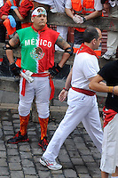 A participant with tshirt with Mexico's colours waits for the Torrestrella's bulls during the fifth bull run of the San Fermin Festival in Pamplona, northern Spain, on July 11, 2013. © Pedro ARMESTRE