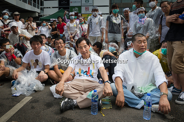 Hong Kong, Government Offices, 28 September 2014<br /> <br /> Middle of the day around the HK government offices. Protesters are prepared against pepper spray and teargas with plastic coats and goggles. Already then the police tries to block the entry and exit points of the area.<br /> <br /> Martin Lee on the front left, a long time democrat and Jimmy Lai, pro-democrat business man and publisher of the Apple daily newspaper, supporting Occupy Central on its first day.<br /> <br /> Photo Kees Metselaar