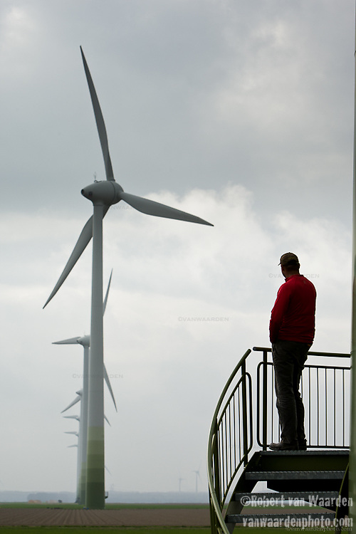 Stephan de Clerk looks down the line of 6 windmills that he helped raise with his neighbours. To satisfy zoning regulations, Stephan had to connect with his immediate neighbours and created a co-operative to produce wind energy. The organization, Samen voor de Wind, means that 6 different landowners all own a windmill and are profiting from the wind energy. It has contributed substantially to the financial well being and health of the farming families.