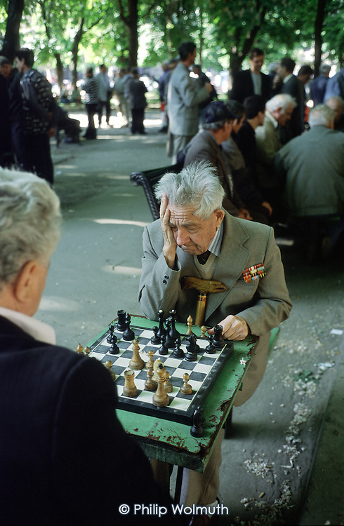 Odessa, Ukraine.A war veteran plays chess in a park in the centre of the city.  The games attract crowds of onlookers and occasional betting.