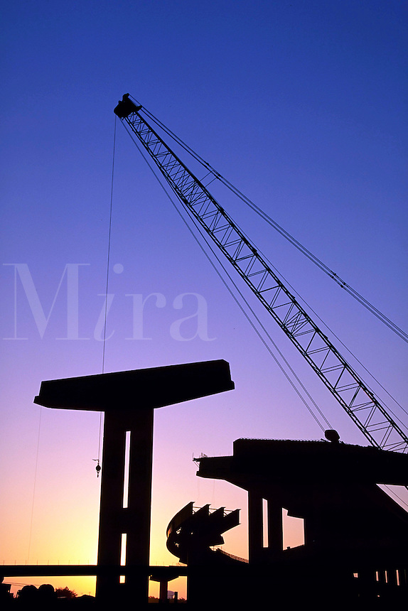 A tall crane is silhouetted as the sun rises on a highway project.