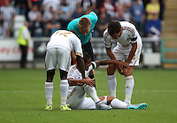 Pictured: Kyle Naughton of Swansea is helped onto his feet by team mates Nathan Dyer, Jack Cork and referee Mike Jones Saturday 15 August 2015<br /> Re: Premier League, Swansea City v Newcastle United at the Liberty Stadium, Swansea, UK.