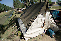 A toddler crawls into a tent in a makeshift camp along a stretch of motorway in Swabi district. Her family, refugees from Swat district, have made camp here because at present there's no space for them in the refugee camps. The Pakistani government began an offensive against the Taliban in the Swat Valley in April 2009, which led to a major humanitarian crisis. Up to two million civilians were estimated to have been displaced by the fighting.