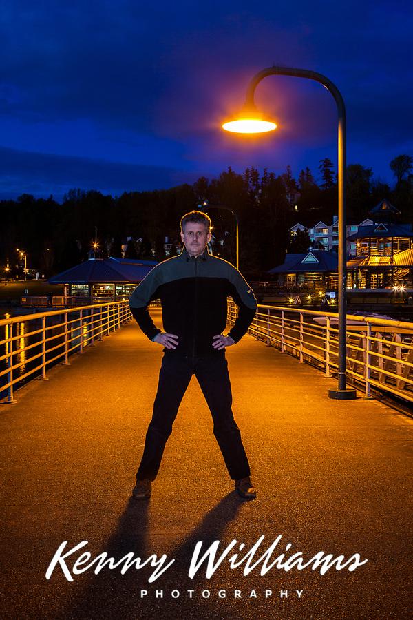 Photographer Kenny Williams standing under lamp post at night on pier, Lake Washington, Renton, WA, USA.