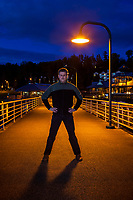 Photographer Kenny Williams standing under lamp post at night on pier, Lake Washington, Renton, WA, USA.