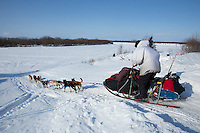 Jerry Sousa drops down the bank onto the river as he leaves the Shageluk checkpoint on Saturday March 9, 2013.  Iditarod Sled Dog Race 2013..Photo by Jeff Schultz copyright 2013 DO NOT REPRODUCE WITHOUT PERMISSION