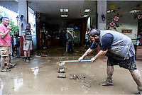 Owners of a local garage try to clear mud and debris from the forecourt in Agia Triada