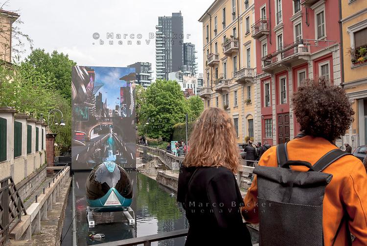 """Milano, Salone del Mobile. """"Aqua"""", Installazione alla conca dell'Incoronata del Naviglio Martesana, raffigurante una Milano futuristica con un mezzo di """"boat sharing"""" sul naviglio reso navigabile --- Milan, Salone del Mobile. """"Aqua"""", installation on the Naviglio Martesana. A futuristic Milan is shown on a led panel and a """"boat sharing"""" capsule lies on the canal turned navigable"""