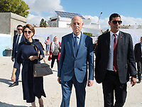 Kais Saied, an independent law professor and presidential candidate (L), arrives at a polling station, accompanied by his wife, in the capital Tunis on October 6, 2019, during the third round of legislative elections