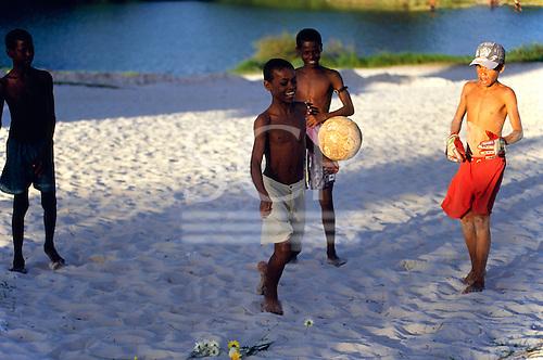 Salvador, Brazil. Young boys playing football barefoot on the sand; Lagoa de Abaete.