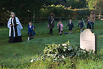 Old Mans Day Braughing Hertfordshire UK. October 2nd 2015. The Rev'd Julie Gawthrope and children from Jenyns First School around the grave of Mathew Wall. Brambles have been placed on the grave as directed in his will to prevent cattle grazing over it.