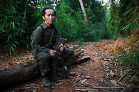 Xang Nou Chue Yang, 53, an ethnic Hmong and a veteran of the CIA Secret War, holds an AK-47 assault rifle while resting along a trail in the jungle of the Vientiane province of Laos on 27 November 2007. Thousands of Hmongs who fought or collaborated with the American CIA until communists took over the country in 1975 remain living hidden in the jungles of Laos