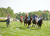 Inaugeration, with Danni Hodsdon at right in the red cap, leads the 5th race field round the clubhouse turn at Mineral Springs. That's Slip Away at far left.