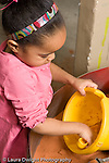 Education Preschool 3-5 year olds sand table girl digging in yellow bucket with scoop vertical