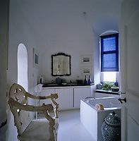 An ornately carved alabaster chair stands at the entrance to this white bathroom