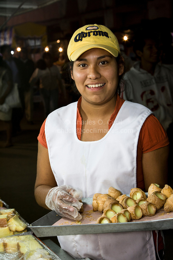 Oaxaca, Mexico, North America.  Day of the Dead Celebrations.  Young Lady Selling Pastries.  Visits to the Cemetery take on a carnival, family atmosphere as parents treat their children to sweets, candies, toys, and amusement rides.  San Miguel Cemetery, Oaxaca.