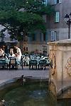 Village fountain, Village square; French sidewalk cafes, Saint Florent; Corsica, France, Mediterranean Coast, Coastal towns in Corsica,