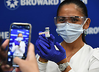 FORT LAUDERDALE, FL - DECEMBER 23: Leonida Lipshy, RN in the COVID unit at the Broward Health Medical Center, shows off a bottle of the Moderna COVID-19 vaccine as Broward Health begins Vaccinating frontline Healthcare caregivers with the Moderna COVID-19 vaccine at Broward Health Medical Center Imperial Point on December 23, 2020 in Fort Lauderdale, Florida. <br /> CAP/MPI04<br /> ©MPI04/Capital Pictures