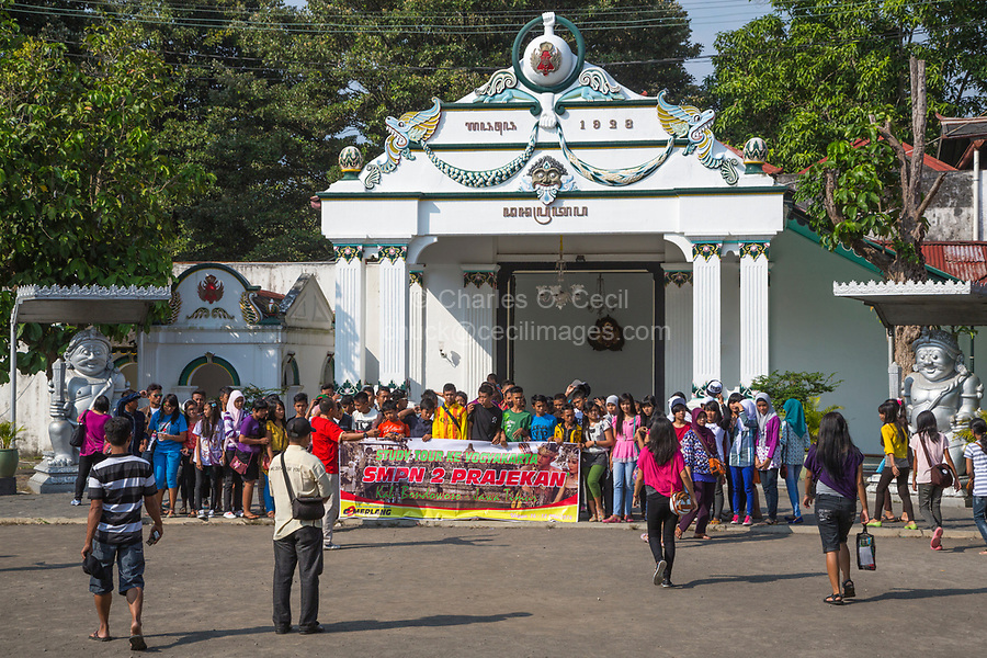 Yogyakarta, Java, Indonesia.  Indonesian Students on a School Trip Pose behind a Banner for a Group Picture before entering the Sultan's Palace.