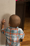 22 month old toddler boy scribbling on wall with crayon
