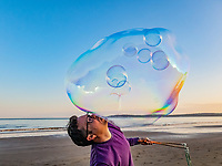 2020 05 07 A man creates giant soap bubbles on a beach of Swansea Bay, Wales, UK