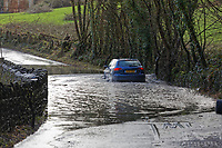 Pictured: A car drives through a flooded road.<br /> Re: Cleanup after storm Dennis in Crickhowell, Wales, UK.